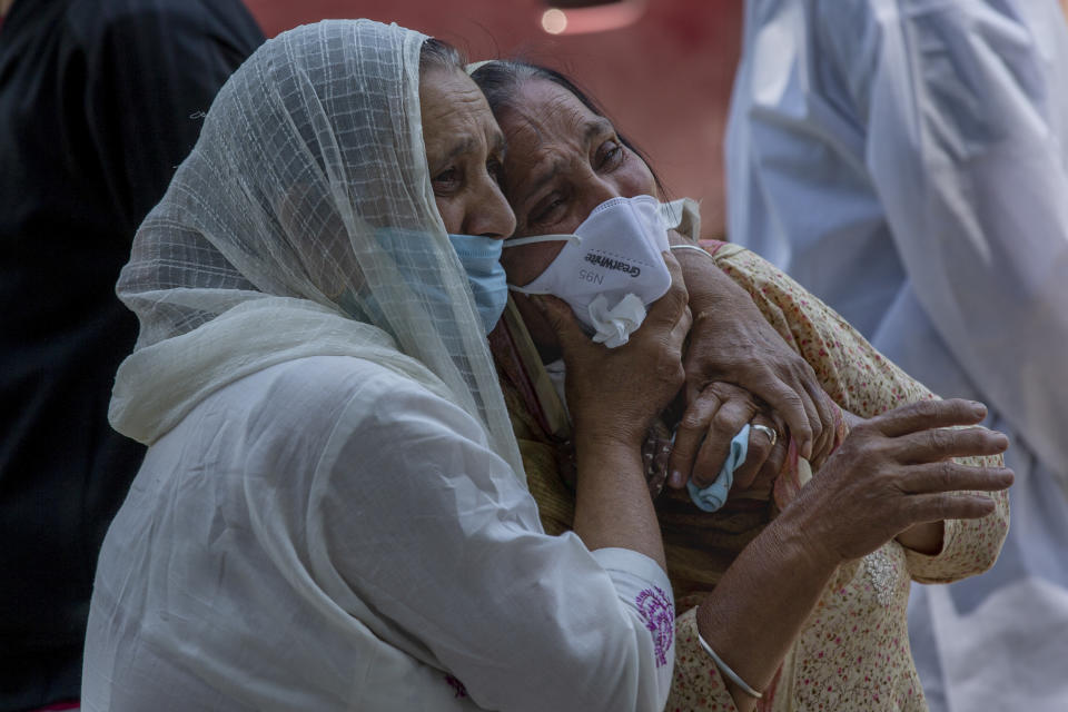 FILE - In this May 28, 2021, file photo, a relative comforts grieving family member of a person who died of COVID-19, at a crematorium in Srinagar, Indian controlled Kashmir. The latest alarming coronavirus variant — the delta variant, first identified in India — is exploiting low global vaccination rates and a rush to ease pandemic restrictions, adding new urgency to the drive to get more shots in arms and slow its supercharged spread. (AP Photo/Dar Yasin, File)