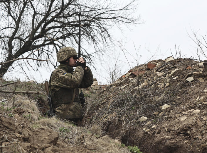 FILE - In this April 12, 2021, file photo, Ukrainian soldier watches through a periscope at fighting positions on the line of separation from pro-Russian rebels near Donetsk, Ukraine. Ukraine and the West have become increasingly worried about the presence of more Russian troops and urged Moscow to pull them back. (AP Photo/File)