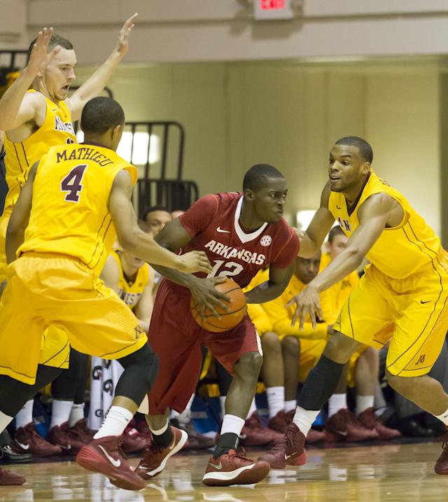 Minnesota forward Oto Osenieks, top left, along with his teammates guard Deandre Mathieu (4) and guard Andre Hollins attempt to trap Arkansas guard Fred Gulley III (12) in the first half of an NCAA college basketball game at the Maui Invitational on Tuesday, Nov. 26, 2013, in Lahaina, Hawaii. (AP Photo/Eugene Tanner)