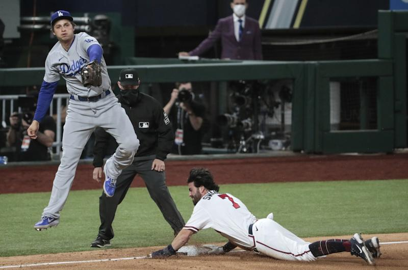 Atlanta Braves baserunner Dansby Swanson slides into third base as Dodgers shortstop Corey Seager catches a late throw.