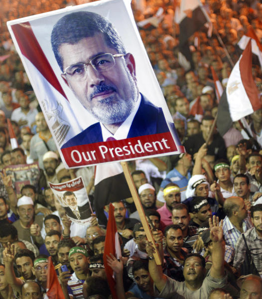 "Supporters of Egypt's ousted President Mohammed Morsi hold his poster and wave national flags as they protest at a park in front of Cairo University, where protesters have installed their camp in Giza, southwest of Cairo, Egypt, Friday, July 19, 2013. Thousands are demonstrating across Egypt to demand the reinstatement of Morsi. His Muslim Brotherhood is mobilizing its followers to march in Cairo and elsewhere Friday for a protest they are dubbing ""Breaking the Coup."" (AP Photo/Amr Nabil)"