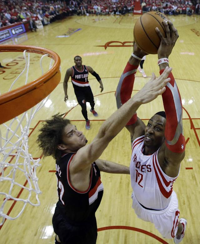 Houston Rockets' Dwight Howard (12) dunks against Portland Trail Blazers' Robin Lopez (42) during the first half in Game 2 of an opening-round NBA basketball playoff series Wednesday, April 23, 2014, in Houston. (AP Photo/David J. Phillip)