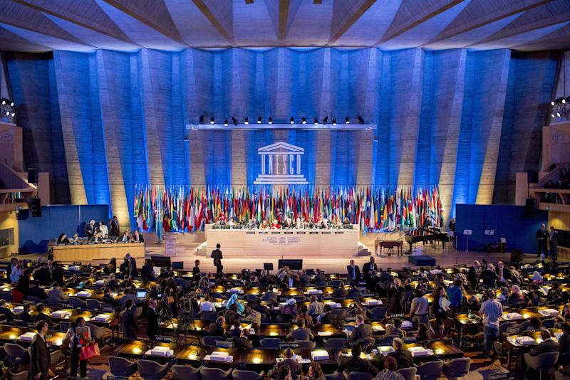 FILE- This Tuesday, Nov. 5, 2013, file photo shows a general view of the UNESCO prior to the opening of General Conference in Paris, France. American influence in culture, science and education around the world will take a high-profile blow on Friday as the US is stripped of its vote at the world's premier cultural agency, UNESCO. The U.S. loses its vote at the Paris-based U.N. Educational, Scientific and Cultural Organization following Washington's decision in 2011 to cut all funding to the U.N. agency over the vote giving Palestine member-state status. (AP Photo/Benjamin Girette, file)