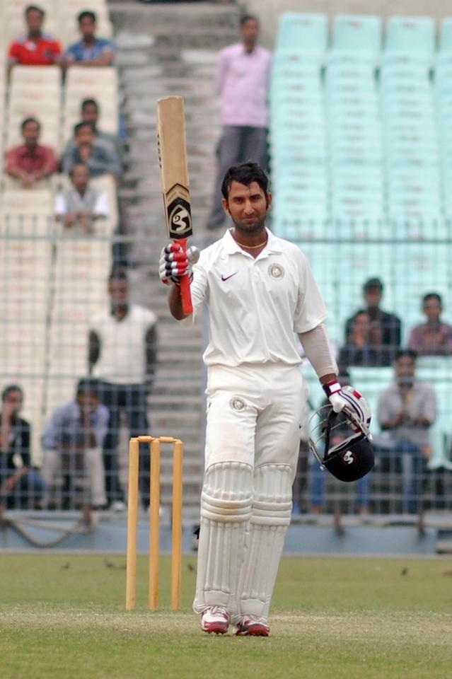 Cheteshwar Pujara celebrates his 150 during a Ranji Trophy match between Bengal and Saurashtra at Eden Gardens in Kolkata on Nov.22, 2013. (Photo: IANS)