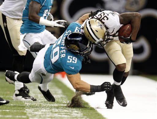 Jacksonville Jaguars linebacker J.K. Schaffer (59) drags down New Orleans Saints running back Travaris Cadet (39) in the second half of a preseason NFL football game in New Orleans, Friday, Aug. 17, 2012. (AP Photo/Jonathan Bachman)