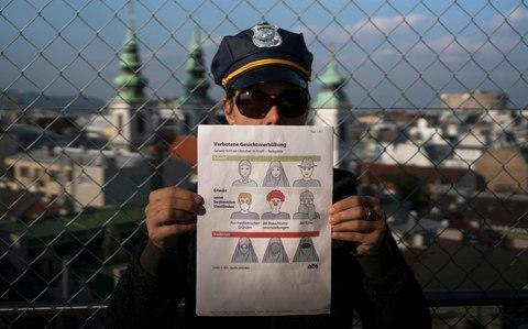 <span>A model holds an information pamphlet about new Austrian restrictions </span> <span>Credit: JOE KLAMAR/AFP/Getty Images </span>