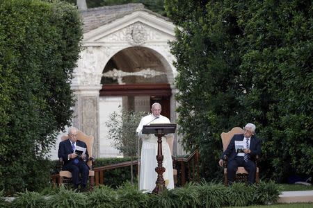 Pope Francis speaks as he is flanked by Israeli President Peres and Palestinian President Abbas in the Vatican Gardens at the Vatican