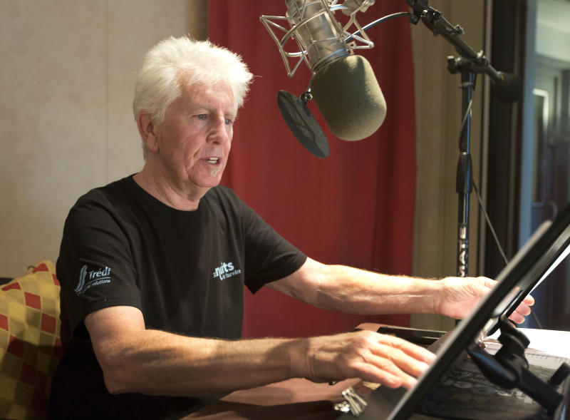 """Singer Graham Nash prepares during the recording session for the audio book version of his """"Wild Tales: A Rock & Roll Life"""" autobiography, in New York, Thursday, July 25, 2013. (AP Photo/Richard Drew)"""