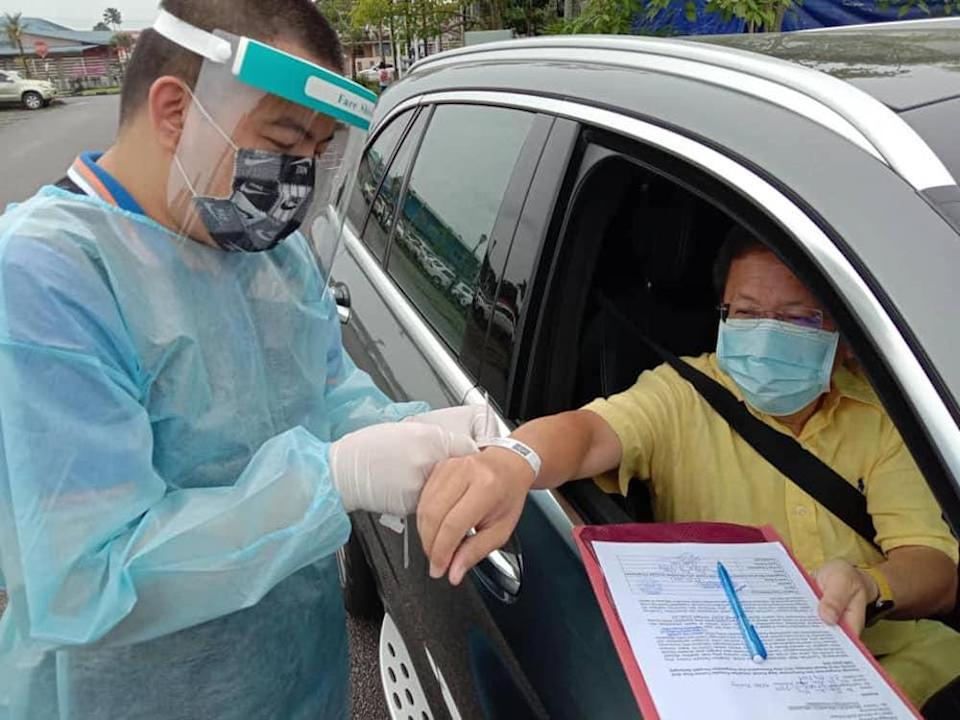 A health care worker putting a wristband on Local Government and Housing Minister Datuk Sri Dr Sim Kui Hian for a home stay order (HSO) after he was exposed to a Covid-19 positive case, January 17, 2021. — Picture courtesy of Facebook/Dr Sim Kui Hian