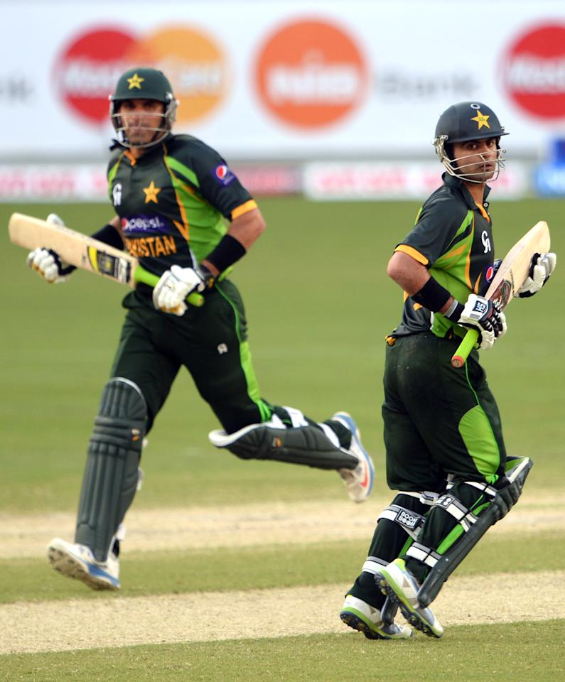 Pakistani cricketers Ahmed Shehzad (R)  and Misbah-ul-Haq (L) make a runs during the second day-night international against South Africa in Dubai Cricket Stadium in Dubai on November 1, 2013. Pakistan's captain Misbah-ul won the toss and decided to bat. AFP PHOTO/ Asif HASSAN        (Photo credit should read ASIF HASSAN/AFP/Getty Images)