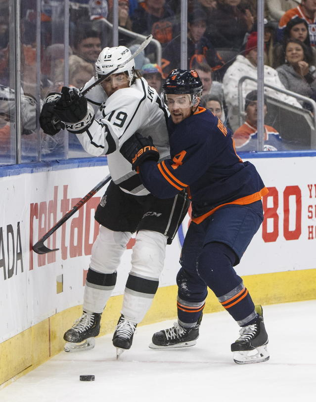 Los Angles Kings' Alex Iafallo (19) is checked by Edmonton Oilers' Kris Russell (4) during the first period of an NHL hockey game Friday, Dec. 6, 2019, in Edmonton, Alberta. (Jason Franson/The Canadian Press via AP)