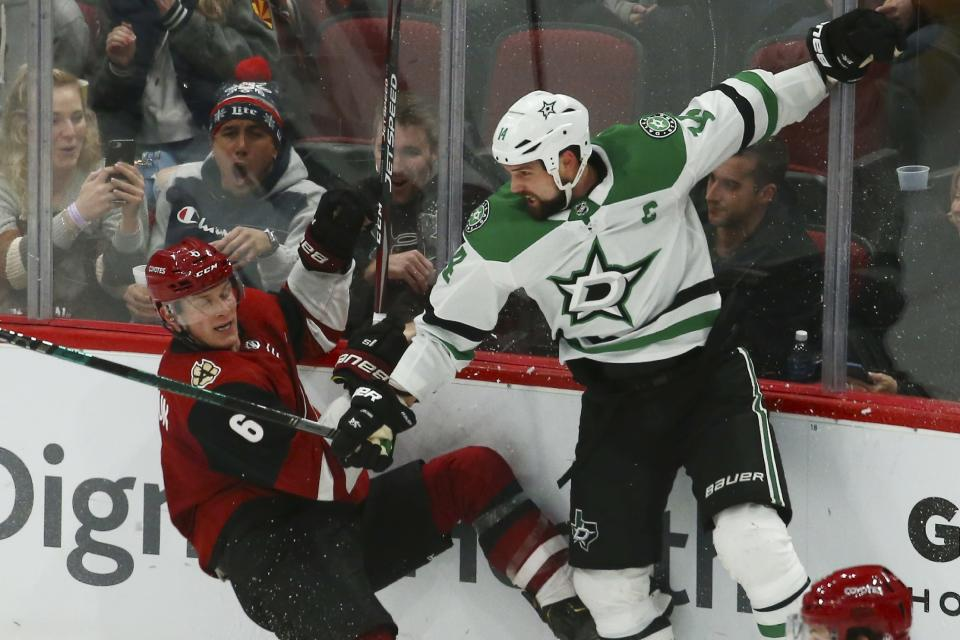 Dallas Stars left wing Jamie Benn, right, checks Arizona Coyotes defenseman Jakob Chychrun (6) to the ice during the second period of an NHL hockey game Sunday, Dec. 29, 2019, in Glendale, Ariz. (AP Photo/Ross D. Franklin)