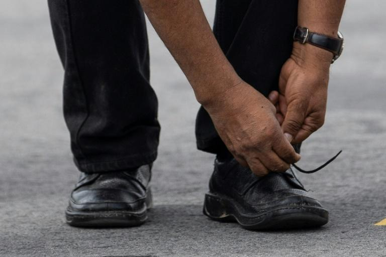 Bolivian ex-President Evo Morales ties his shoe upon landing in Mexico City, on November 12, 2019, where he was granted asylum after his resignation (AFP Photo/Pedro PARDO)