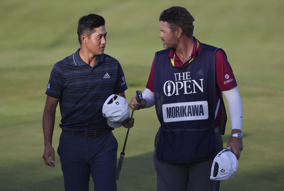 United States' Collin Morikawa, left, walks off the 18th green with his caddie Jonatha Jakovac after he completed his third round at the British Open Golf Championship at Royal St George's golf course Sandwich, England, Saturday, July 17, 2021. (AP Photo/Ian Walton)