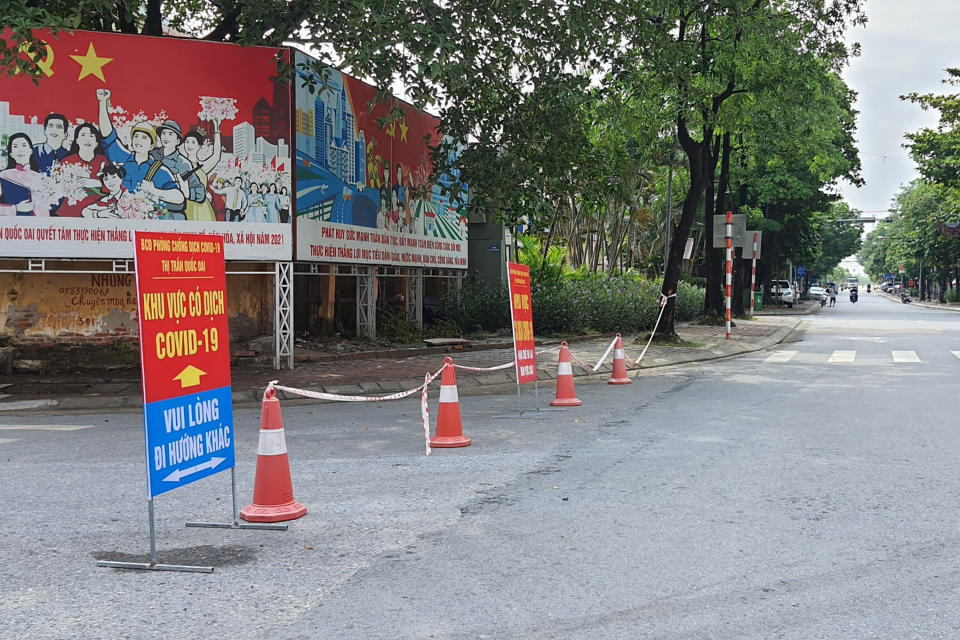 A street is cordoned off to control the traffic in Hanoi, Vietnam, Saturday, July 24, 2021. Vietnam announced a 15-day lockdown in the capital Hanoi starting Saturday as a coronavirus surge spread from the southern Mekong Delta region. (AP Photo/Hieu Dinh)