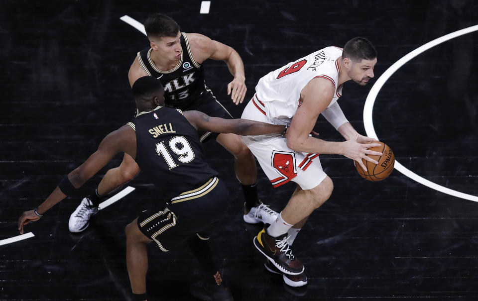 Chicago Bulls' Nikola Vucevic, right, drives the ball away from Atlanta Hawks' Tony Snell (19) and Bogdan Bogdanovic (13) during the second half of an NBA basketball game Friday, April 9, 2021, in Atlanta. (AP Photo/Ben Margot)