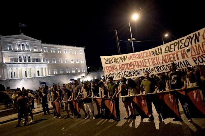 Some 6,000 anti-austerity demonstrators staged a mass protested near the Greek parliament ahead of the parliamentary debate in Athens, on July 23, 2015 (AFP Photo/Aris Messinis )