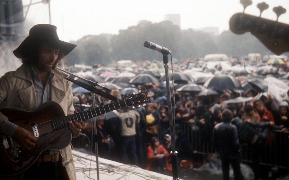 Chapman entertains a rain-soaked festival in the late 1960s - Alain Dister/Dalle/Retna Pictures/Dalle/Avalon