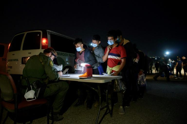Children and adolescents are processed at a makeshift 'office' by a Border Patrol agent after reaching Roma, Texas late on March 27, 2021