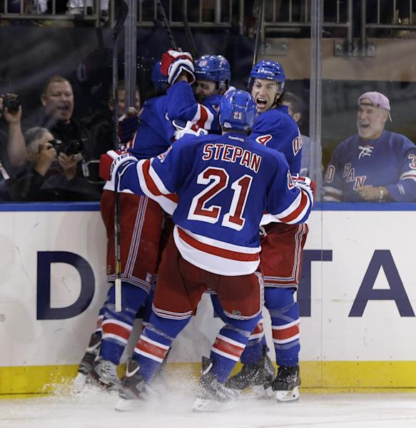 The New York Rangers, including Michael Del Zotto, right, Derek Stepan (21), Chris Kreider, second from left, and Rick Nash, left, celebrate after Kreider scored the winning goal during the overtime period in Game 4 of the Eastern Conference semifinals in the NHL hockey Stanley Cup playoffs, Thursday, May 23, 2013. The Rangers won 4-3. (AP Photo/Seth Wenig)
