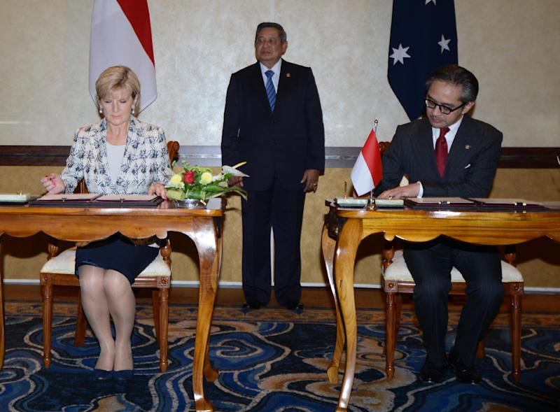 Indonesian President Susilo Bambang Yudhoyono (C) witnesses Australian Foreign Minister Julie Bishop and her Indonesian counterpart Marty Natalegawa signing documents during a ceremony in Nusa Dua, Bali, on August 28, 2014 (AFP Photo/Sonny Tumbelaka)