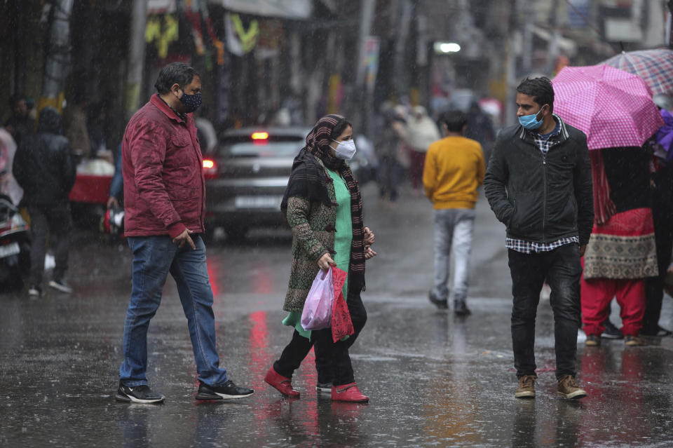 Indians, wearing face masks as a precautionary measure against the coronavirus walk at a market during rain in Jammu, India, Sunday, Jan.3, 2021. India authorized two COVID-19 vaccines on Sunday, paving the way for a huge inoculation program to stem the coronavirus pandemic in the world's second most populous country. (AP Photo/Channi Anand)