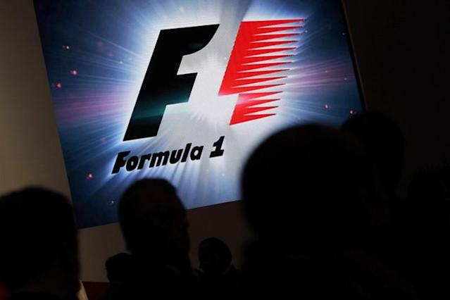 FILE PHOTO: Reporters are silhouetted by a screen showing a F1 logo during a news conference to announce a Formula One race in Mexico City