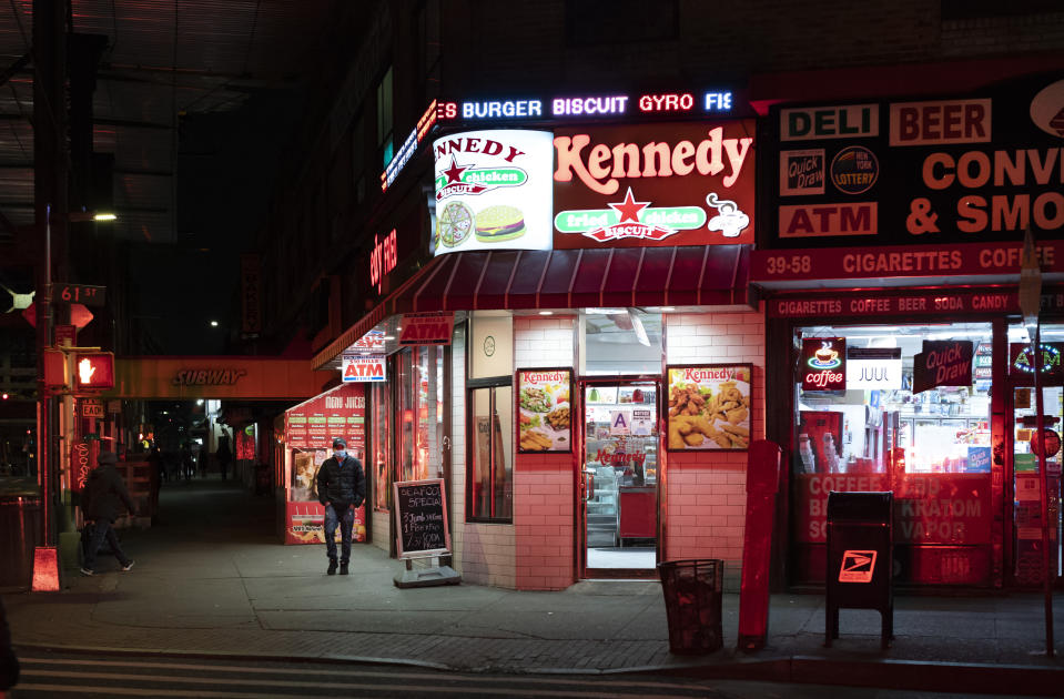A man walks past an open Kennedy Fried Chicken restaurant in the Queens borough of New York, Thursday night, April 23, 2020, during the coronavirus pandemic. The New York City immortalized in song and scene has been swapped out for the last few months with the virus version. In all the unknowing of what the future holds, there's faith in that other quintessential facet of New York City: that the city will adapt. (AP Photo/Mark Lennihan)