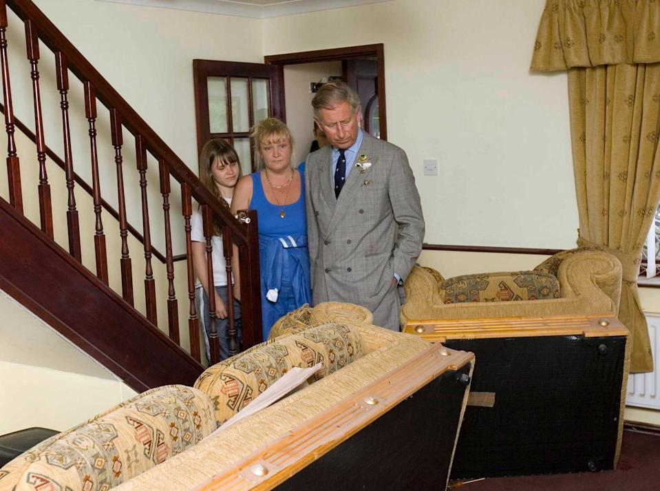 Prince Charles, Prince of Wales sees flood damage in the home of the Breeze family when he visits the village of Carcliffe in South Yorkshire to meet emergency service personnel and residents affected by the recent floods brought on by heavy rains.