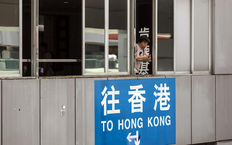 A man looks out from a window as a sign directing travelers towards Hong Kong is displayed near the Luohu border crossing in Shenzhen - Bloomberg