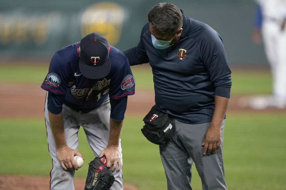 Minnesota Twins starting pitcher Jake Odorizzi, left, is checked on by a trainer after getting hit by a batted ball during the fourth inning of a baseball game against the Kansas City Royals at Kauffman Stadium in Kansas City, Mo., Friday, Aug. 21, 2020. Odorizzi left the game. (AP Photo/Orlin Wagner)