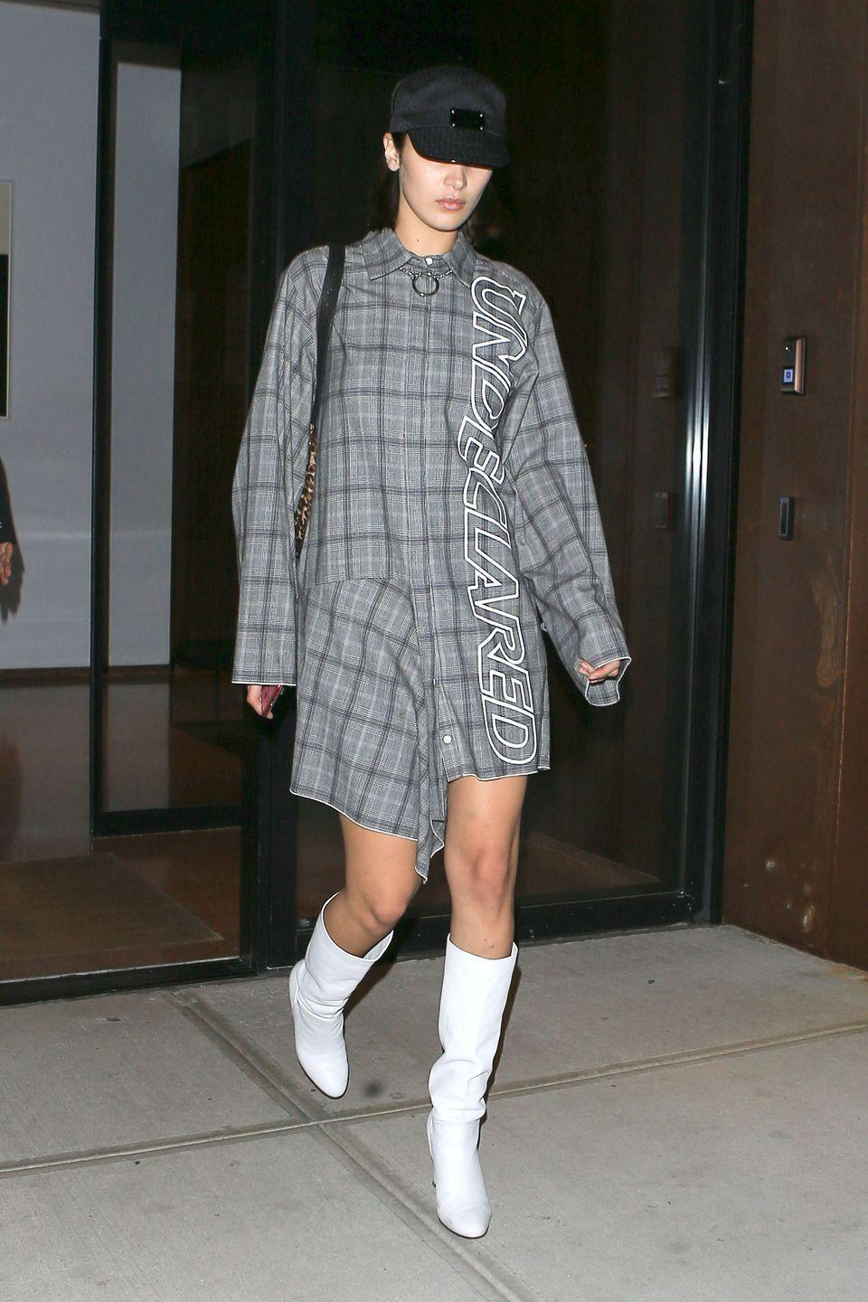 """<p>In a conductor hat, plaid """"Undeclared"""" shirt dress by Leo, leopard print bag, and white knee-high boots while out in New York.</p>"""