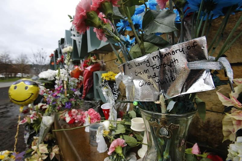 File--In this Dec. 19, 2012, file photo, a note memorializing two victims is surrounded by flowers and balloons at the Clackamas Town Center mall entrance in Portland, Ore., a week after a gunman opened fire in the mall, killing the two people and himself.   Law authorities released a 950-page report, Wednesday, May 1, 2013, on the shooting where a gunman blazed away with a military-style semiautomatic rifle as people did their Christmas shopping. (AP Photo/Don Ryan, file)