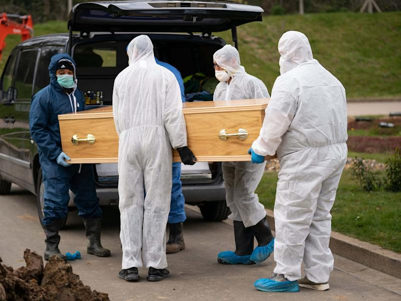 Undertakers wearing personal protective equipment carry the coffin during the funeral in the Eternal Gardens Muslim Burial Ground, Chislehurst of Ismail Mohamed Abdulwahab, 13, from Brixton, south London: PA
