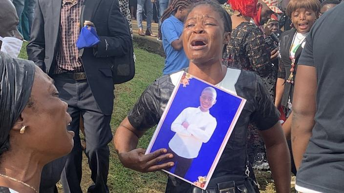 A mourner clutched a photo of one of the dead children