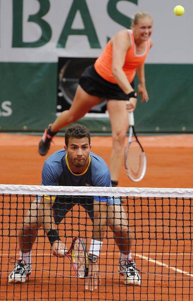 Germany's Anna-Lena Groenefeld, behind, serves the ball, as Netherlands' Jean-Julien Rojer waits at the net during the mixed doubles final of the French Open tennis tournament at the Roland Garros stadium, in Paris, France, Thursday, June 5, 2014. (AP Photo/David Vincent)