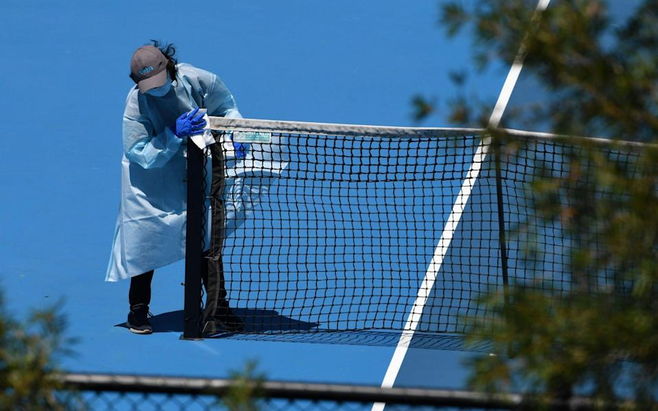 People wearing personal protective equipment are seen disinfecting a tennis court after a training session at Melbourne Park - JAMES ROSS/EPA-EFE/Shutterstock