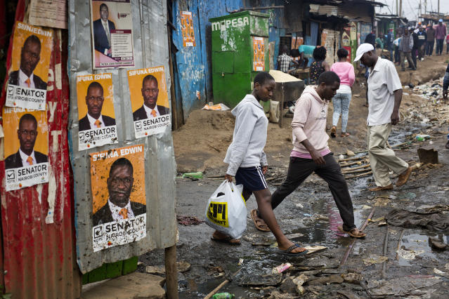 <p>Kenyans walk past election posters in the Kibera slum in Nairobi, Kenya, Monday Aug. 7, 2017. (Photo: Jerome Delay/AP) </p>