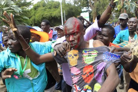 A supporter of Kenya's opposition bleeds from a head injury while engaging with riot police before their rally at the Uhuru park grounds in the capital Nairobi