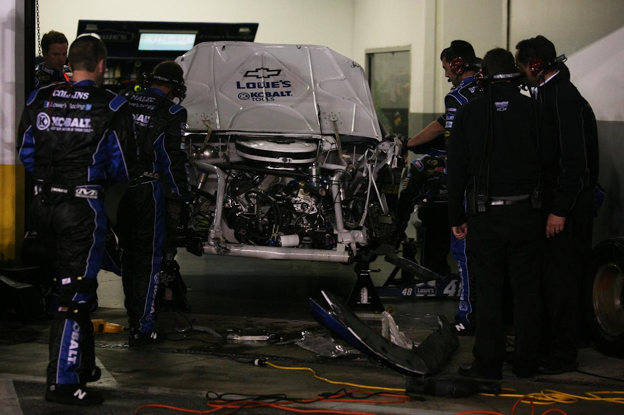 DAYTONA BEACH, FL - FEBRUARY 27:  Crew members work on the #48 Lowe's Chevrolet driven by Jimmie Johnson in the garage after being involved in an on track incident during the NASCAR Sprint Cup Series Daytona 500 at Daytona International Speedway on February 27, 2012 in Daytona Beach, Florida.  (Photo by Jerry Markland/Getty Images for NASCAR)