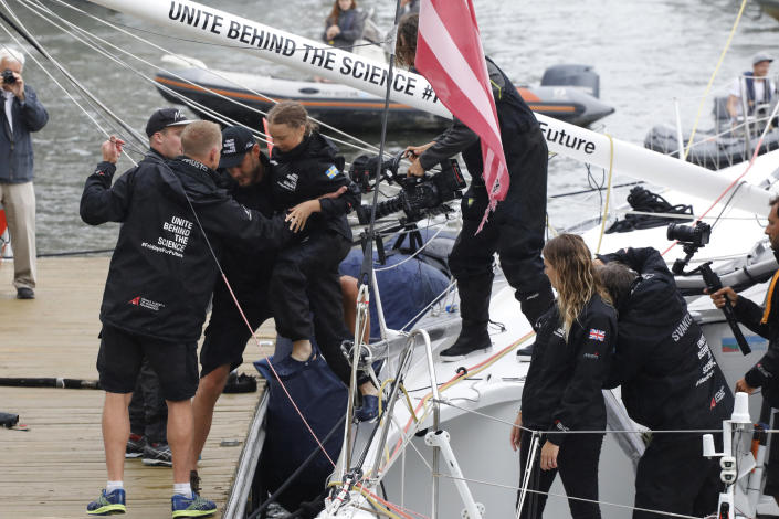 Greta Thunberg, center left, a 16-year-old Swedish environmental activist, is helped from the Malizia II as she arrives in New York, Wednesday, Aug. 28, 2019. The zero-emissions yacht left Plymouth, England on August 14. Thunberg is scheduled to address the United Nations Climate Action Summit on Sept. 23. (AP Photo/Mark Lennihan)