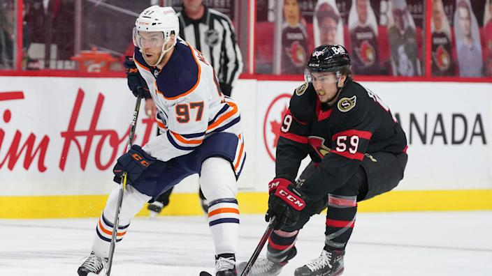 OTTAWA, ON - APRIL 7:  Connor McDavid #97 of the Edmonton Oilers skates up ice with the puck against Alex Formenton #59 of at Canadian Tire Centre on April 7, 2021 in Ottawa, Ontario, Canada.  (Photo by André Ringuette/NHLI via Getty Images)