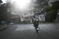 """Motorcycle stuntman Pedro Aldana performs a wheelie on his motorbike as he rides to an exhibition along the old highway from Caracas to La Guaira, Venezuela, Sunday, Jan. 10, 2021. Aldana, who prefers his show name """"Crazy Pedro,"""" dares to beat the odds and put on exhibitions of speed and agility with a crew of like-minded daredevils atop their motorcycles. (AP Photo/Matias Delacroix)"""