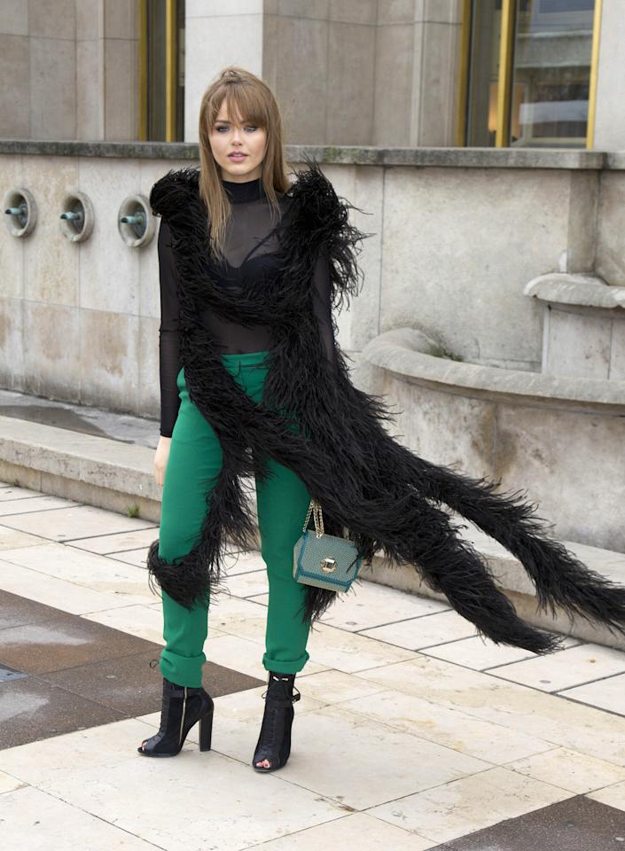 <p>The blogger, who made a statement in green pants, kept her sheer top covered by what looks like a long feathered vest. (<i>Splash News)</i></p>