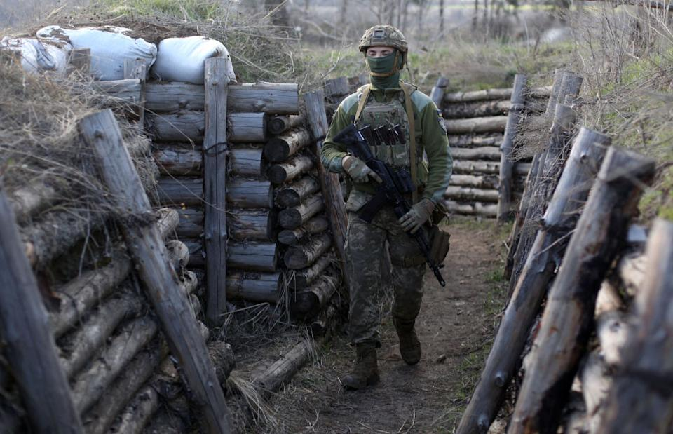 A Ukrainian serviceman patrols along a trench in Schastya, Lugansk region, near the frontline with Russia backed separatists.