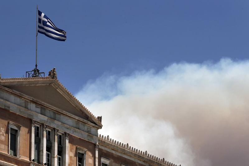 A Greek national flag flutters atop the parliament building as smoke from a raging wildfire rises in Athens