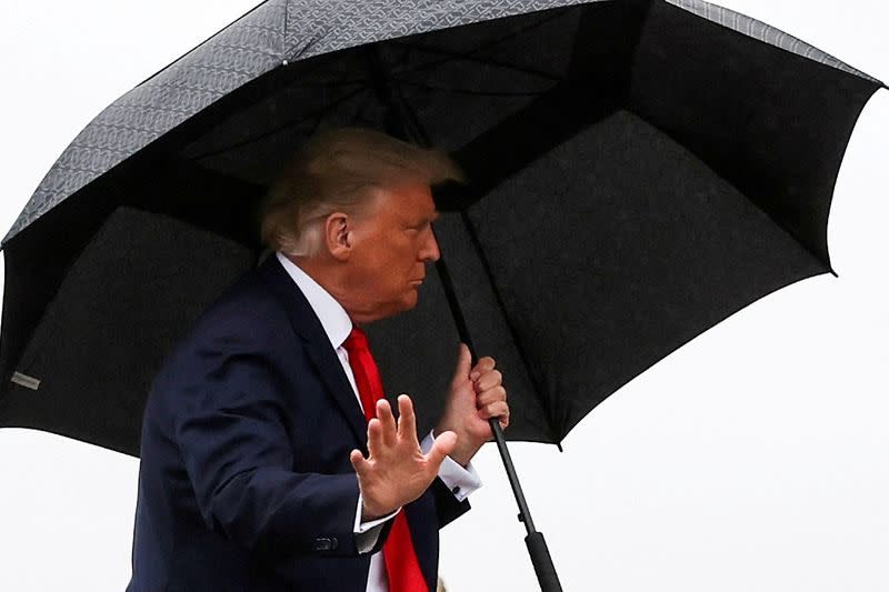 FILE PHOTO: U.S. President Donald Trump carries an umbrella while boarding Air Force One at Joint Base Andrews, Maryland