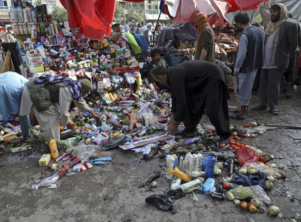 People inspect the site of a deadly bomb explosion in Kabul, Afghanistan, Tuesday, July 13, 2021. The bomb killed several people and wounded over 10 others, Kabul police officias said on Tuesday. It comes as the U.S. all but winds up its 'forever war' in Afghanistan and a day after the outgoing commander Gen. Scott Miller warned increasing violence reduced the chances of finding a peaceful end to decades of war. (AP Photo/Rahmat Gul)
