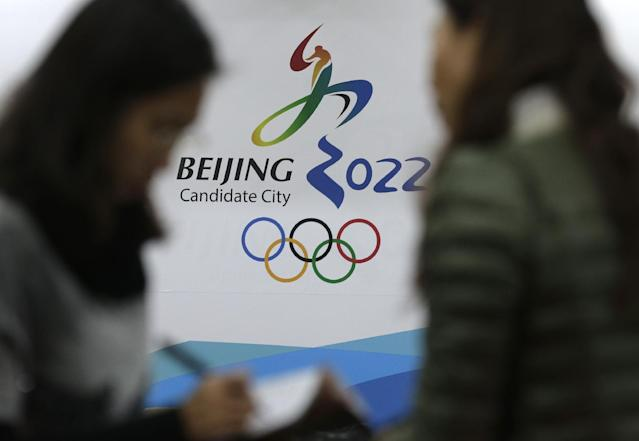 Journalists chat near the Beijing's bid for the 2022 Winter Olympics logo after attending a media briefing by Chinese officials, at the Beijing Olympics Headquarters in Beijing, China Tuesday, Nov. 4, 2014. The new front-runner to host the 2022 Winter Olympics doesn't have a long winter sports tradition. Just 20 years ago, there were fewer than 10,000 skiers in China - out of a then-population of 1.2 billion. (AP Photo/Andy Wong)