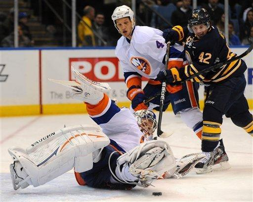 New York Islanders goaltender Evgeni Nabokov (20) makes a save as Buffalo Sabres forward Nathan Gerbe (42) looks for a rebound while being checked by Islanders defenseman Mark Eaton (4) in the first period of their NHL hockey game, Saturday, Jan. 14, 2012, in Uniondale, N.Y. (AP Photo/John Dunn)